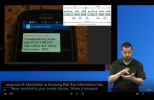 Screenshot of video playing, shows photo of mobile phone receiving a tornado warning, the WEA vibrating cadence, ASL interpreter, and captions.